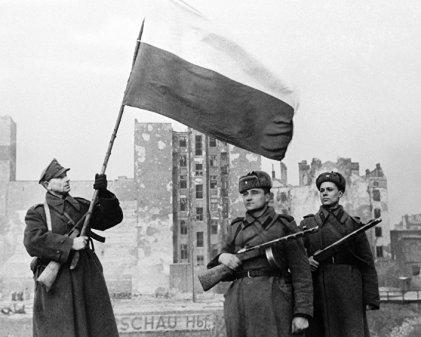 żołnierz polski z flagą biało czerwoną i dwaj radzieccy żołnierze 1945 r