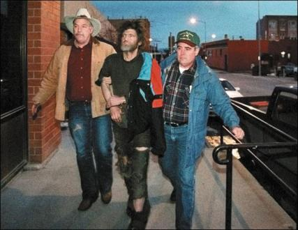 Theodore Kaczynski is escorted by two FBI officers into a Helena office building on the night of his arrest in 1996. Printed with permission from photographer Greg Rec