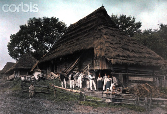 1927, Ruthenia, Ukraine --- A large group of peasants stand outside their thatch-roof homes --- Image by © Hans Hildenbrand/National Geographic Society/Corbis