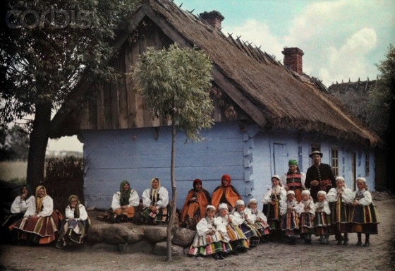 1933, Poland --- Lowicz residents sit in front of abbey church in their Sunday best --- Image by © Hans Hildenbrand/National Geographic Society/Corbis